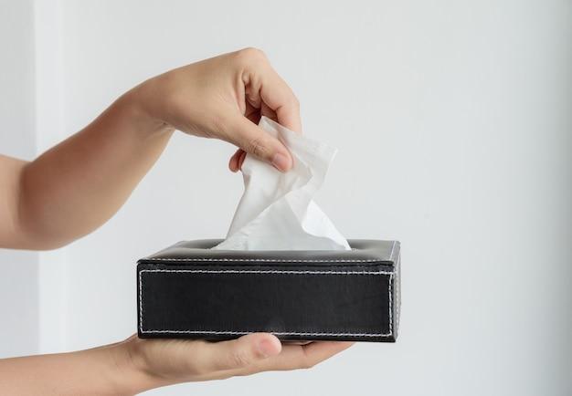 Женщина рука, сбор белой салфеткой из коробки ткани.