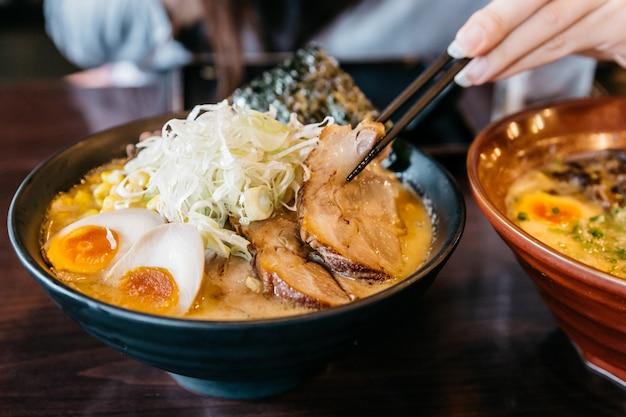 Woman hand pinching noodle in ramen pork bone soup (tonkotsu ramen).