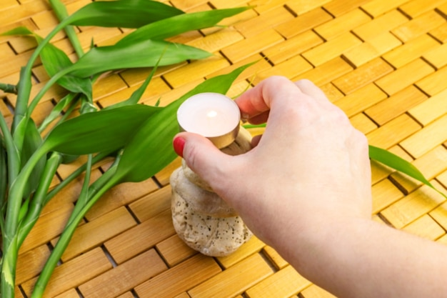 Woman hand placing lighting candle on white stone pyramid with bamboo leaves on wooden mat