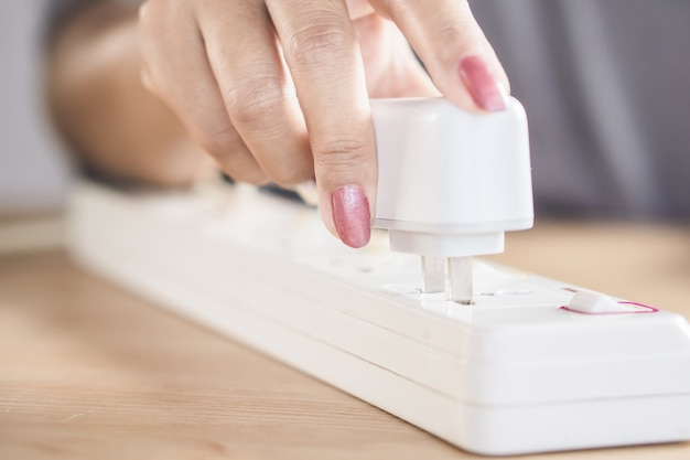 Woman hand plug in electric on socket to charge mobile phone