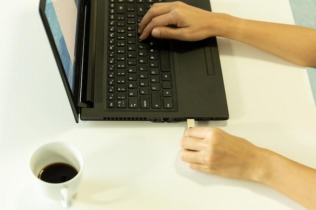 Рука женщины затыкая привод usb на компьтер-книжке с чашкой кофе в офисе.