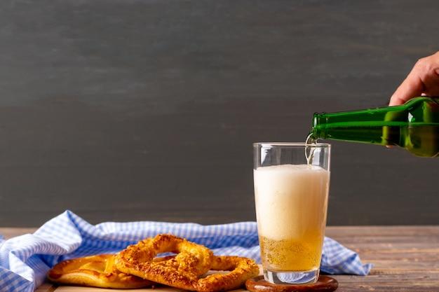 여자 손 나무 테이블에 맥주를 붓는입니다.