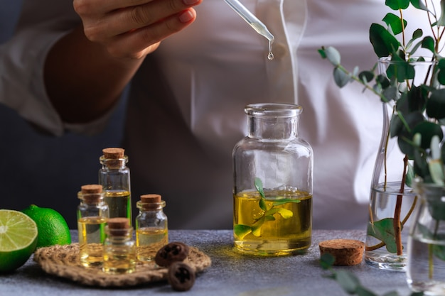 Woman hand pouring eucalyptus essential oil into bottle on grey table