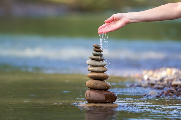 Woman hand pouring water on stones balanced like pyramid