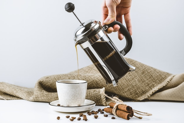 Woman hand pours brewed coffee in a french press