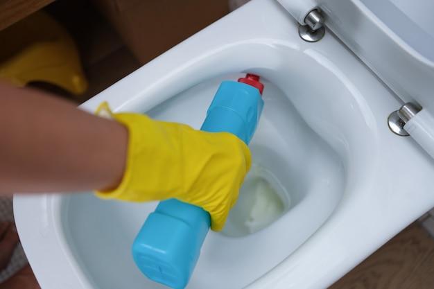 女性の手が便器のクローズアップに洗浄剤を注ぐ