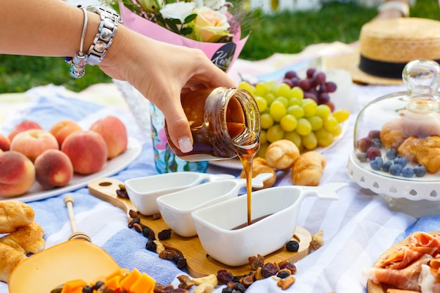 Woman hand pours honey from transparent bottle to sauceboat, at summer picnic background