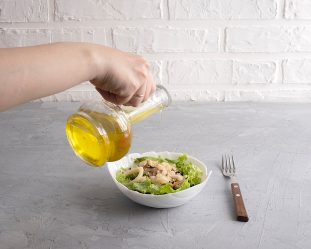 Woman hand pours olive oil on fresh warm seafood salad
