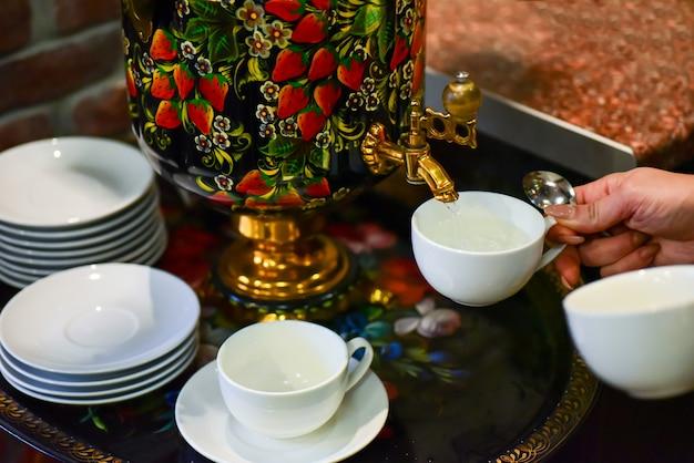 女性の手がサモワールからお茶を注ぐ