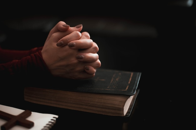 Woman hand praying on holy bible in the morning.