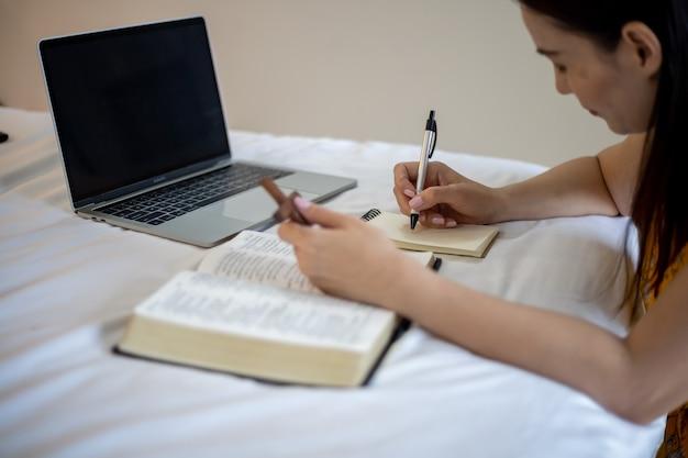 아침에 성경에 기도하는 여자 손. 온라인 예배로 성경을 공부하세요.