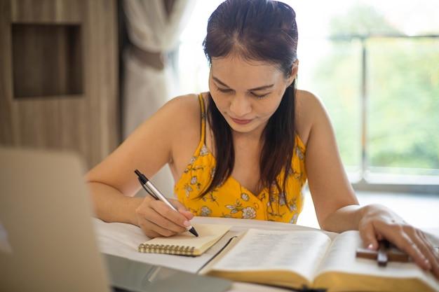 Рука женщины молится на библии утром. изучайте библию с онлайн-поклонением.