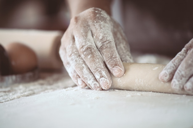 Woman hand preparing bread dough for baking cookies in the kitchen