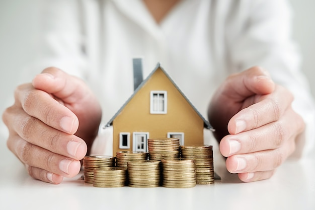 Woman hand protecting on  stack coins and house model on table.