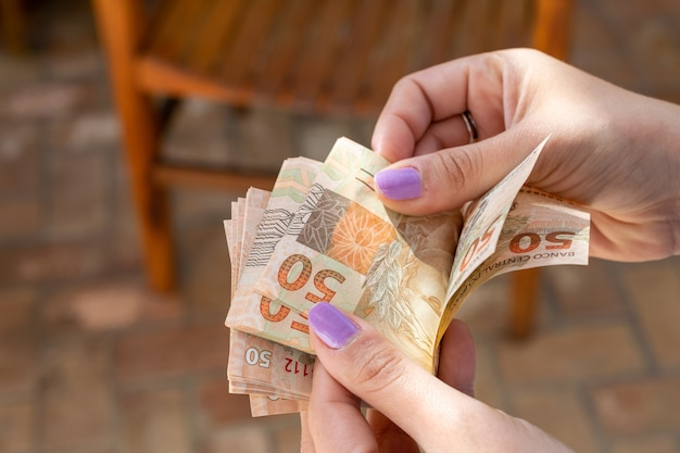 Woman hand providing brazilian money banknotes