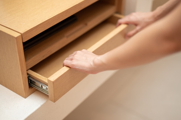 Woman hand pull open drawer wooden cabinet.