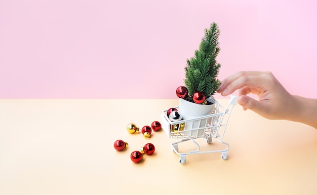 カートまたはトロリーとクリスマスの飾りのモックアップを押す女性手