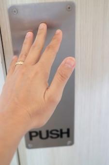 여자 손으로 문을 밀어