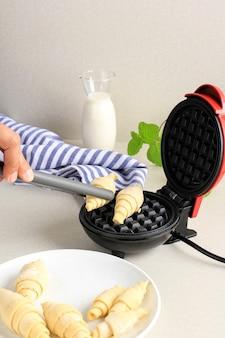 女性の手は、灰色のトングを使用して冷凍ワッフルを電気ミニワッフルメーカーに入れました。朝食用の自家製クロワッサンワッフル(クロワッフル)を作る。