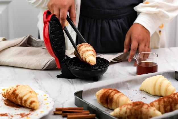 Женщина рукой кладет замороженные вафли в электрическую мини-вафельницу с помощью серых щипцов