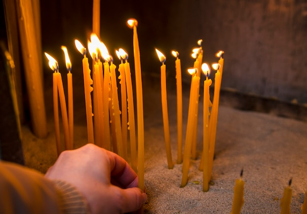 Woman hand put wax candle on flame for pray in church. beewax candles burn in temple