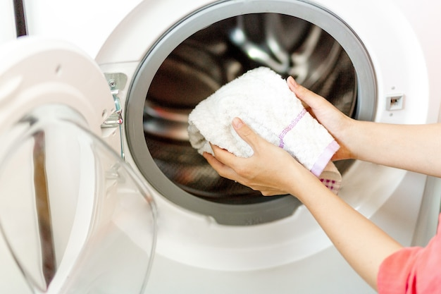 여자 손은 세탁기에 흰 수건을 넣었다. 주부는 집에서 세탁을 합니다.