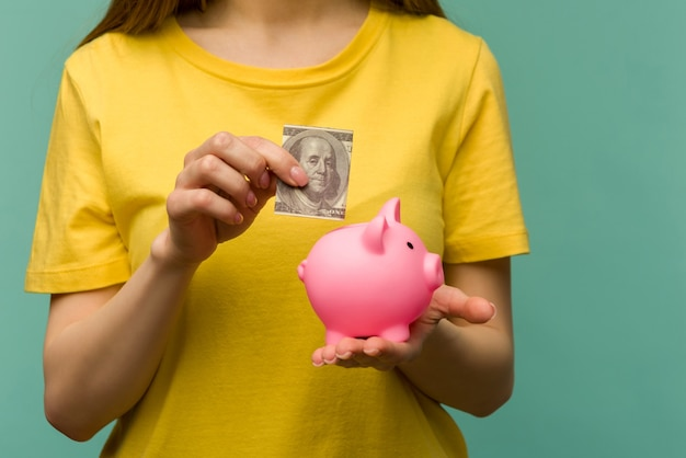 Woman hand putting 100 dollars into piggy for saving money wealth and financial concept.- image