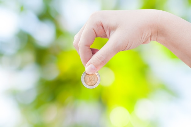 Рука женщины кладет монету на зеленую природу