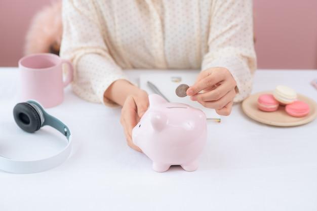 貯金箱、屋内にコインを置く女性の手