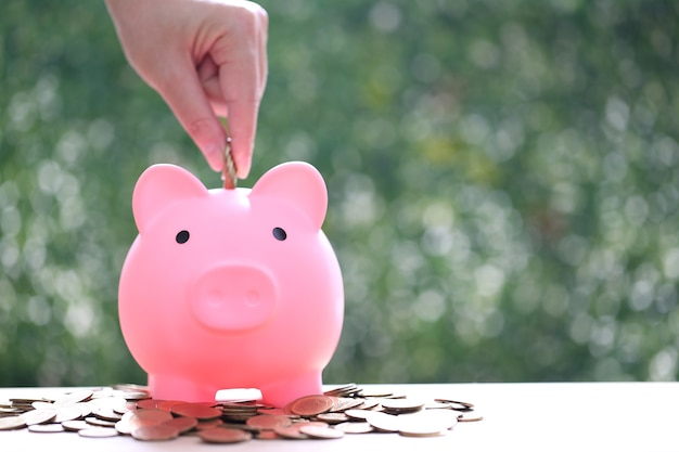 Woman hand putting a coin into piggy bank on green background