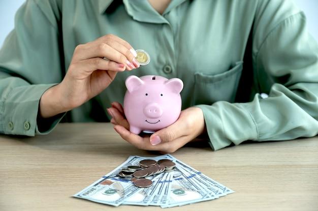 여자 손 돼지 저금통에 동전을 넣어, 미래 계획 및 퇴직 기금 개념에 대 한 돈을 절약.