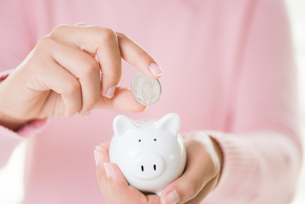 Woman hand putting coin into piggy bank. saving money wealth and financial concept