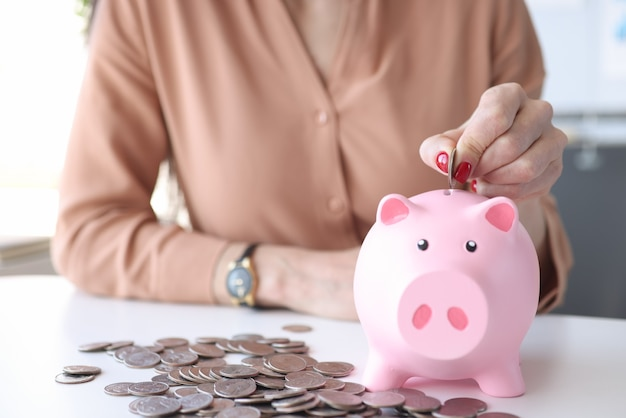 Woman hand putting coin into pink piggy bank closeup