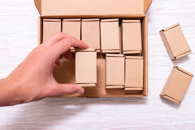 Woman hand putting lot of small cardboard boxes inside of large case with cover