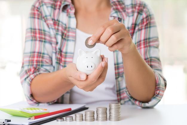 Woman hand putting money coin into piggy bank. saving money concept.