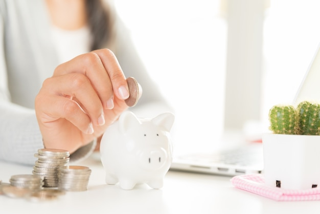 Woman hand putting money coin into piggy bank with stack of coins. saving money