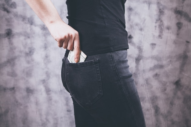 Рука женщины кладет деньги в карман джинсов
