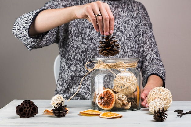 Woman hand putting pinecone in glass jar