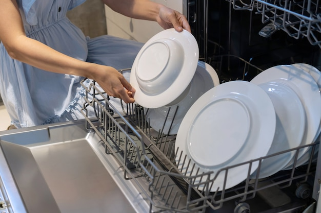 Woman hand putting a plate in the dishwasher.