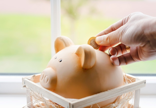 Woman hand putting pound coin into piggy bank, saving for retirement or pension concept