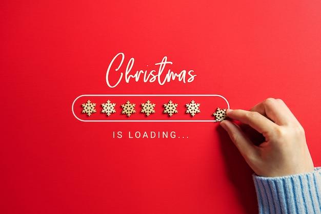 Woman hand putting snowflakes christmas loading bar
