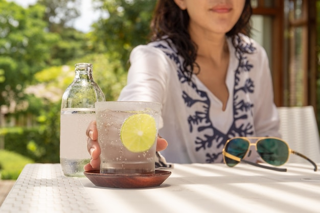 Woman hand reachinf glass of healthy nutrition of sparkling water.