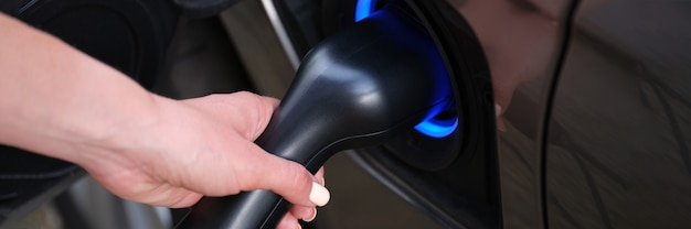 Woman hand refueling car with electricity using cable closeup