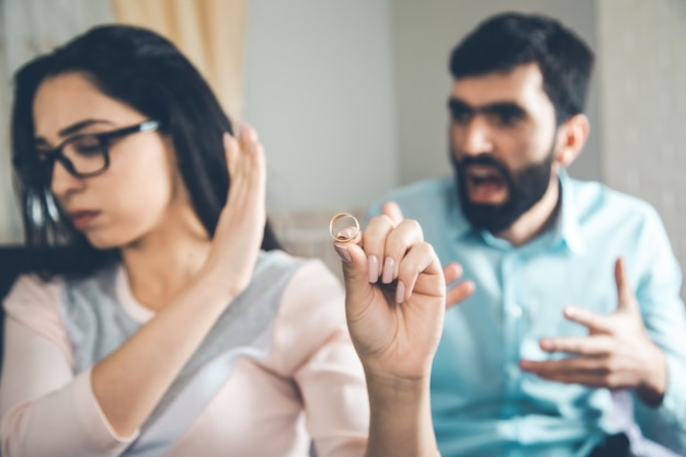 Woman hand ring with angry man in home