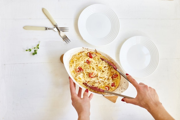 Женская рука готовит трендовые вирусные запеченные помидоры и фета с макаронами, фетапаста на белой деревянной поверхности. новое, популярное блюдо для ужина, вид сверху, копия пространства.