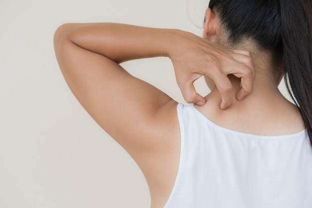 Woman hand scratch the itch by hand at neck and back. healthcare and medical concept.