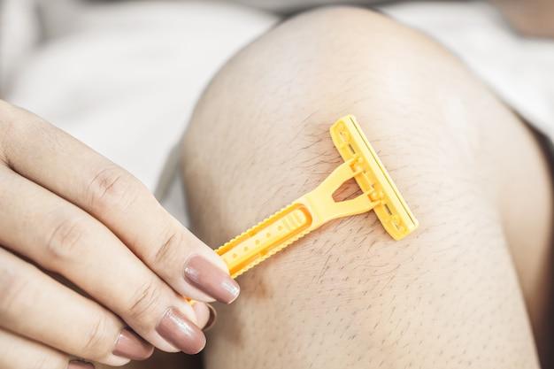 Woman hand shaving her hair legs closeup