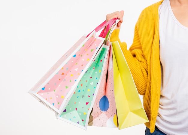 여자 손 그녀는 여러 가지 빛깔의 쇼핑백을 들고 노란색 셔츠를 입고
