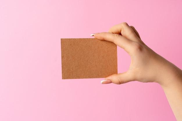 Рука женщины показывая пустую визитную карточку на розовой стене.