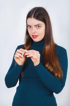 깨진 된 담배를 보여주는 여자 손. 건강에 해로운 생활 방식